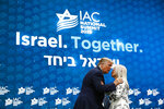 President Donald Trump embraces Miriam Adelson, the wife of Las Vegas Sands Corporation Chief Executive and Republican mega donor Sheldon Adelson, as she introduces him at the Israeli American Council National Summit in Hollywood, Fla., Saturday, Dec. 7, 2019. (AP Photo/Patrick Semansky)