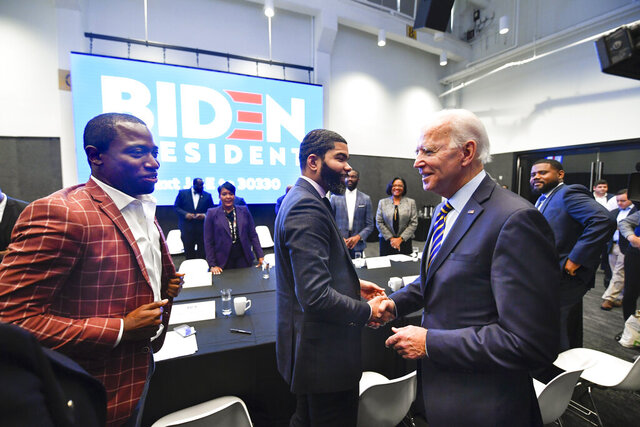 FILE - In this Nov. 21, 2019, file photo, Democratic presidential candidate former Vice President Joe Biden, right, walks around a table meeting with an assembly of Southern black mayors including Mississippi Mayor Chokwe Lumumba and Virginia Mayor Levar Stoney, left, in Atlanta. Biden is leading the most diverse presidential field in history among black voters. (AP Photo/John Amis, File)