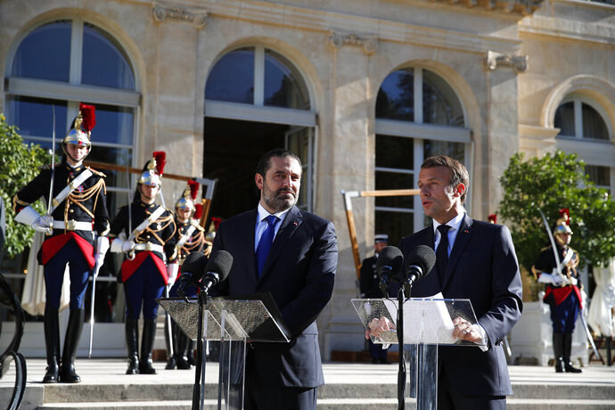 French President Emmanuel Macron, right, and Lebanese Prime Minister Saad Hariri answer reporters in the garden of the Elysee Palace, Friday, Sept. 20, 2019 in Paris. (AP Photo/Francois Mori)