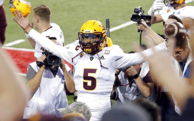 Arizona State quarterback Manny Wilkins celebrates with the fans after defeating Arizona in an NCAA college football game, Saturday, Nov. 24, 2018, in Tucson, Ariz. (AP Photo/Rick Scuteri)
