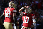 San Francisco 49ers quarterback Jimmy Garoppolo (10) celebrates a play offensive guard Mike Person (68) during the first half of an NFL divisional playoff football game against the Minnesota Vikings, Saturday, Jan. 11, 2020, in Santa Clara, Calif. (AP Photo/Marcio Jose Sanchez)