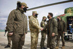 Ukrainian President Volodymyr Zelenskiy shakes hands a soldier as he visits the war-hit Donbas region, eastern Ukraine, Thursday, April 8, 2021. Ukraine is at the center of a major geopolitical battle in the eastern part of the country with Moscow backed separatists. (Ukrainian Presidential Press Office via AP)