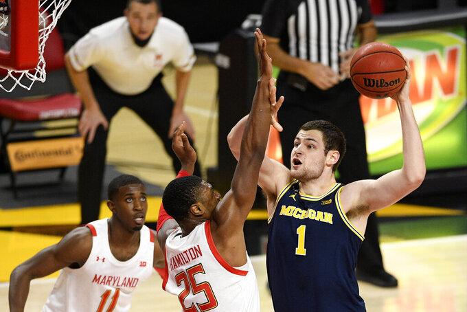 Michigan center Hunter Dickinson (1) goes to the basket next to Maryland forward Jairus Hamilton (25) and guard Darryl Morsell (11) during the first half of an NCAA college basketball game, Thursday, Dec. 31, 2020, in College Park, Md. (AP Photo/Nick Wass)