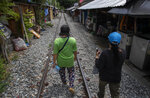 Darunee Khedkhow, right and Jariya Saekean, teachers of Makkasan preschool, walk along a railway line to deliver meals in Bangkok, Thailand, Wednesday, June 24, 2020. During the third month that schools remained closed due to the coronavirus outbreak,  teachers have cooked meals, assembled food parcels and distributed them to families in this community sandwiched between an old railway line and a khlong, one of Bangkok's urban canals. (AP Photo/Gemunu Amarasinghe)