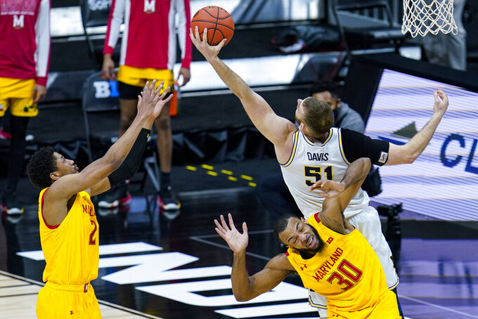 Michigan forward Austin Davis (51) grabs a rebound over Maryland forward Galin Smith (30) and guard Aaron Wiggins (2) in the first half of an NCAA college basketball game at the Big Ten Conference tournament in Indianapolis, Friday, March 12, 2021. (AP Photo/Michael Conroy)