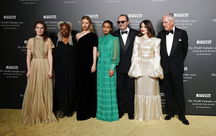 From left, Stella Roversi, American actress Whoopi Goldberg, British model Mia Goth, American model Yara Shahidi, Italian photographer Paolo Roversi, British actress Claire Foy and Pirelli CEO Marco Tronchetti Provera pose for photographers at the 2020 Pirelli Calendar event in Verona, Italy, Tuesday, Dec. 3, 2019. (AP Photo/Antonio Calanni)