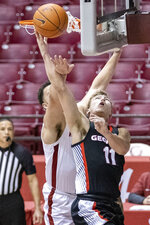 Georgia guard Jaxon Etter (11) gets by Alabama forward Alex Reese (3) for a shot during the first half of an NCAA basketball game on Saturday, Feb. 13, 2021, in Tuscaloosa, Ala. (AP Photo/Vasha Hunt)