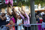 """Children reach for a stuffed throw during a parade dubbed """"Tardy Gras,"""" to compensate for a cancelled Mardi Gras due to the COVID-19 pandemic, in Mobile, Ala., Friday, May 21, 2021. (AP Photo/Gerald Herbert)"""