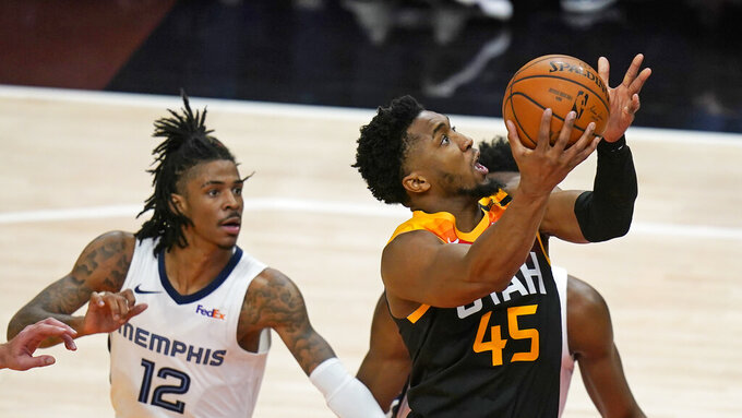 Utah Jazz guard Donovan Mitchell (45) goes to the basket as Memphis Grizzlies guard Ja Morant (12) watches during the second half of Game 2 of their NBA basketball first-round playoff series Wednesday, May 26, 2021, in Salt Lake City. (AP Photo/Rick Bowmer)