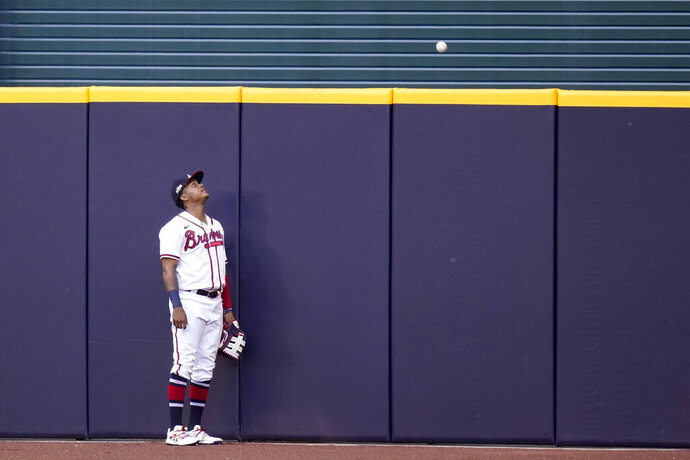 Atlanta Braves center fielder Cristian Pache watches a home run ball by Los Angeles Dodgers Edwin Rios during the first inning in Game 3 of a baseball National League Championship Series Wednesday, Oct. 14, 2020, in Arlington, Texas. (AP Photo/Eric Gay)