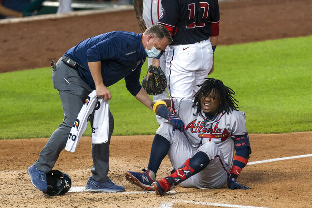 Atlanta Braves' Ronald Acuna Jr., grimaces as he is helped after fouling the ball off his left foot during the fourth inning of the team's baseball game against the Washington Nationals in Washington, Friday, Sept. 11, 2020. Acuna was helped off the field. (AP Photo/Manuel Balce Ceneta)