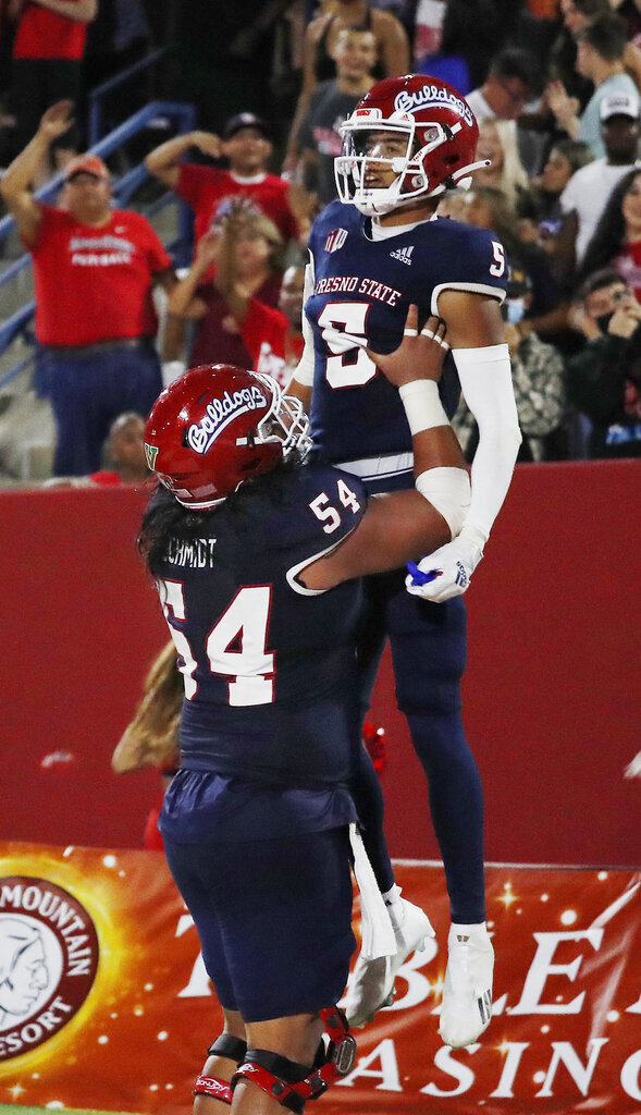 Fresno State offensive lineman Bula Schmidt holds up wide receiver Jalen Cropper after a touchdown against UNLV during the second half of an NCAA college football game in Fresno, Calif., Friday, Sept. 24, 2021. (AP Photo/Gary Kazanjian)