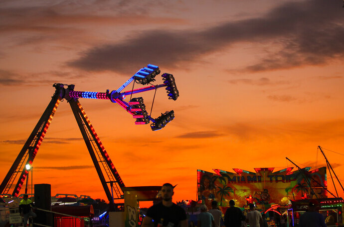 In this picture taken Thursday, Sept. 12, 2019, rides are backdropped by the sunset sky at an autumn fair in Titu, southern Romania. Romania's autumn fairs are a loud and colorful reminder that summer has come to an end and, for many families in poorer areas of the country, one of the few affordable public entertainment events of the year. (AP Photo/Vadim Ghirda)