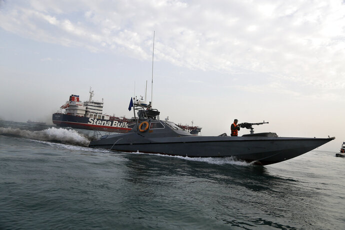 FILE - In this July 21, 2019 file photo, a speedboat of the Iran's Revolutionary Guard moves around a British-flagged oil tanker, the Stena Impero, which was seized by the Guard, in the Iranian port of Bandar Abbas. The U.S. Navy is trying to put together a new coalition of nations to counter what it sees as a renewed maritime threat from Iran. Meanwhile, Iran finds itself backed into a corner and ready for a possible conflict. It stands poised on Friday, Sept. 6, 2019, to further break the terms of its 2015 nuclear deal with world powers. (Hasan Shirvani/Mizan News Agency via AP, File)