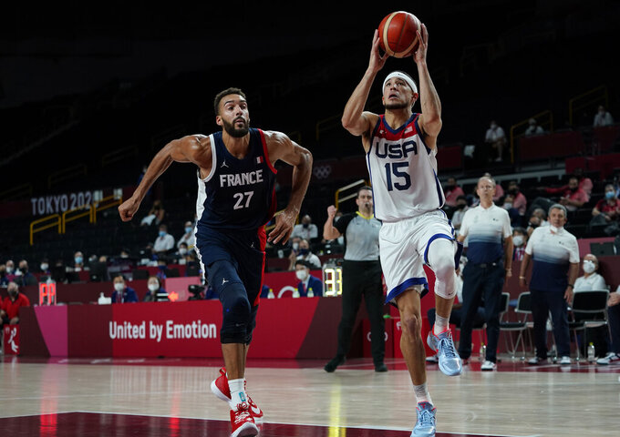 United States' Devin Booker (15) drives to the basket ahead of France's Rudy Gobert (27) during men's basketball gold medal game at the 2020 Summer Olympics, Saturday, Aug. 7, 2021, in Saitama, Japan. (AP Photo/Charlie Neibergall)