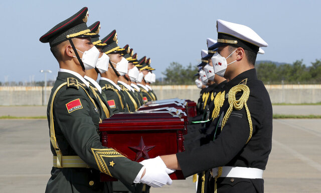 In this photo provided by the South Korea Defense Ministry, Chinese honor guard members, left, receive caskets containing the remains of Chinese soldiers from South Korean honor guards during the handing over ceremony at the Incheon International Airport in Incheon, South Korea, Sunday, Sept. 27, 2020. The remains of 117 Chinese soldiers who died in the 1950-53 Korean War were returned to China on Sunday in an annual repatriation delayed this year by the coronavirus outbreak. (South Korea Defense Ministry via AP)