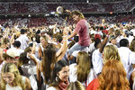 Arkansas fans rush the field to celebrate Arkansas' win over Texas in an NCAA college football game Saturday, Sept. 11, 2021, in Fayetteville, Ark. (AP Photo/Michael Woods)