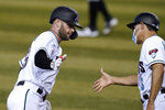 Arizona Diamondbacks' Christian Walker, left, celebrates his two-run home run against the Colorado Rockies with third base coach Tony Perezchica during the third inning during the first game of a baseball doubleheader Friday, Sept. 25, 2020, in Phoenix. (AP Photo/Ross D. Franklin)