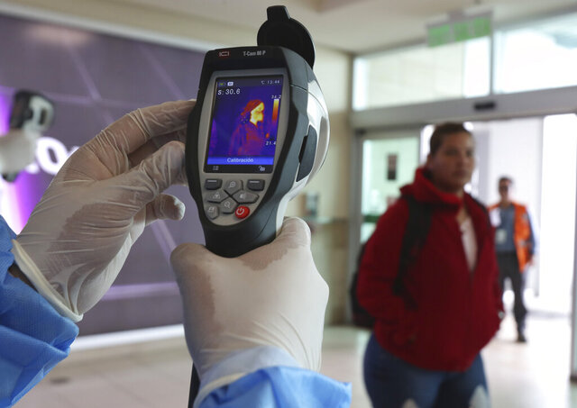 A Health Ministry staffer monitors the body temperature of travelers deplaning from international flights at the Mariscal Sucre Airport, in Quito, Ecuador, Saturday, Feb. 29, 2020. Officials in Ecuador on Saturday confirmed the first case of the new coronavirus in the South American nation. (AP Photo/Dolores Ochoa)