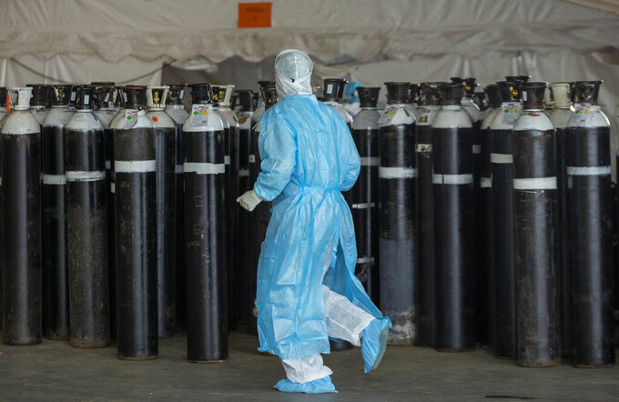 FILE - In this Jan. 11, 2021, file photo, a health worker in a protective suit runs past oxygen cylinders in a makeshift emergency unit for COVID-19 patients at Steve Biko Academic Hospital in Pretoria, South Africa. In South Africa, with by far the largest number of COVID-19 cases and deaths in Africa, officials warn of a new surge as the Southern Hemisphere's winter approaches.  (AP Photo/Themba Hadebe, File)