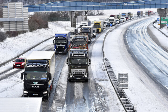 Trucks and cars make their way in the snow D8 highway near the village of Libouchec, Czech Republic, Wednesday, Feb. 5, 2020.  Authorities across eastern Europe have issued warnings for strong winds,  heavy rain and snow that toppled trees, damaged buildings and closed roads throughout the region.(Ondrej Haket/CTK via AP)