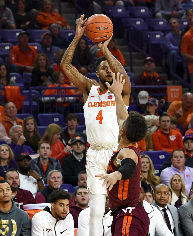 Clemson's Shelton Mitchell (4) shoots a 3-pointer over Virginia Tech's Wabissa Bede during the first half of an NCAA college basketball game Saturday, Feb. 9, 2019, in Clemson, S.C.. (AP Photo/Richard Shiro)