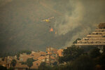A helicopter makes a water drop over a wildfire in Estepona, Spain, Thursday, Sept. 9, 2021. Nearly 800 people have been evacuated from their homes and road traffic has been disrupted as firefighting teams and planes fight a wildfire in southwestern Spain. (AP Photo/Sergio Rodrigo)