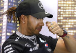 Mercedes driver Lewis Hamilton of Britain rubs his nose during a press conference at the Australian Formula One Grand Prix in Melbourne, Thursday, March 12, 2020. Six-time world champion Lewis Hamilton has questioned the wisdom of staging the season-opening Formula One Grand Prix while other sports are canceling events because of the spreading coronavirus. (AP Photo/Rick Rycroft)