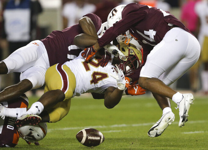 Boston College Running back Pat Garwo III, center, fumbles the ball while being tackled by Virginia Tech defenders Divine Deablo, left, and Devin Taylor, right, in the first half of an NCAA college football game against Boston College in Blacksburg Va. Saturday, Oct. 17, 2020. (Matt Gentry/The Roanoke Times via AP, Pool)