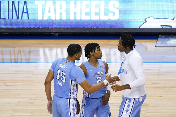 North Carolina forward Garrison Brooks (15) and North Carolina guard Caleb Love (2) greet North Carolina forward Sterling Manley (21) after their win over Virginia Tech after an NCAA college basketball game in the quarterfinal round of the Atlantic Coast Conference tournament in Greensboro, N.C., Thursday, March 11, 2021. UNC won the game 81-73. (AP Photo/Gerry Broome)