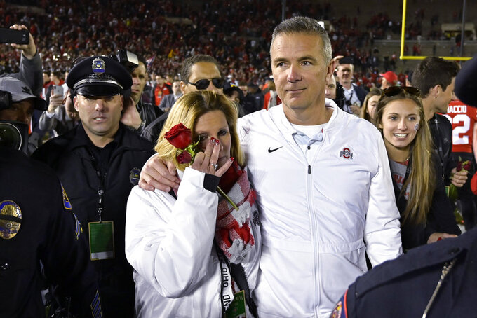 Ohio State coach Urban Meyer and his wife, Shelley, left, leave the field after Ohio State defeated Washington 28-23 in the Rose Bowl NCAA college football game Tuesday, Jan. 1, 2019, in Pasadena, Calif. (AP Photo/Mark J. Terrill)