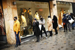 People, wearing face masks to prevent the spread of the coronavirus, wait in line to enter a shop in a commercial street in downtown Brussels, Tuesday, Dec. 1, 2020. Non-essential shops in Belgium are reopening on Tuesday in the wake of encouraging figures about declining infection rates and hospital admissions because of the coronavirus. (AP Photo/Francisco Seco)