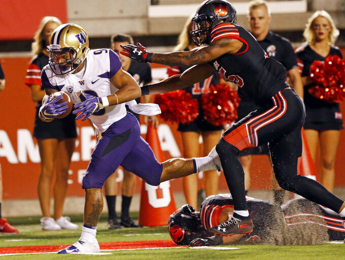 FILE - In this Sept. 15, 2018, file photo, Washington running back Myles Gaskin (9) scores in front of Utah defensive back Corrion Ballard, right, during the first half of an NCAA college football game in Salt Lake City. The teams meet again Friday night for the Pac-12 championship. (AP Photo/Rick Bowmer, File)