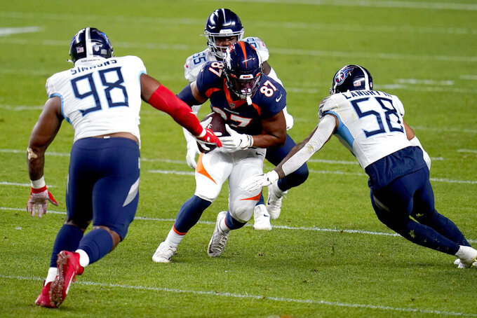 Denver Broncos tight end Noah Fant (87) makes as catch as Tennessee Titans linebacker Harold Landry (58) and defensive tackle Jeffery Simmons (98) defend during the first half of an NFL football game, Monday, Sept. 14, 2020, in Denver. (AP Photo/Jack Dempsey)
