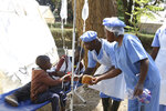 Health workers offer food to a father and son suffering from cholera symptoms at a local hospital in Harare, Tuesday, Sept, 11, 2018.  A cholera emergency has been declared in Zimbabwe's capital after 20 people have died, the health minister said Tuesday. (AP Photo/Tsvangirayi Mukwazhi)