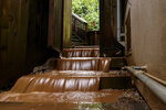 Water rushes down the stairs of a house near a mudslide that destroyed three homes on a hillside in Sausalito, Calif., Thursday, Feb. 14, 2019. Waves of heavy rain pounded California on Thursday, filling normally dry creeks and rivers with muddy torrents, flooding roadways and forcing residents to flee their homes in communities scorched by wildfires. (AP Photo/Michael Short)