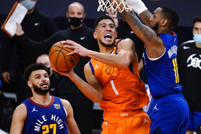 Phoenix Suns guard Devin Booker (1) drives between Denver Nuggets guard Jamal Murray and Monte Morris (11) during the second half of an NBA basketball game Friday, Jan. 22, 2021, in Phoenix. (AP Photo/Rick Scuteri)