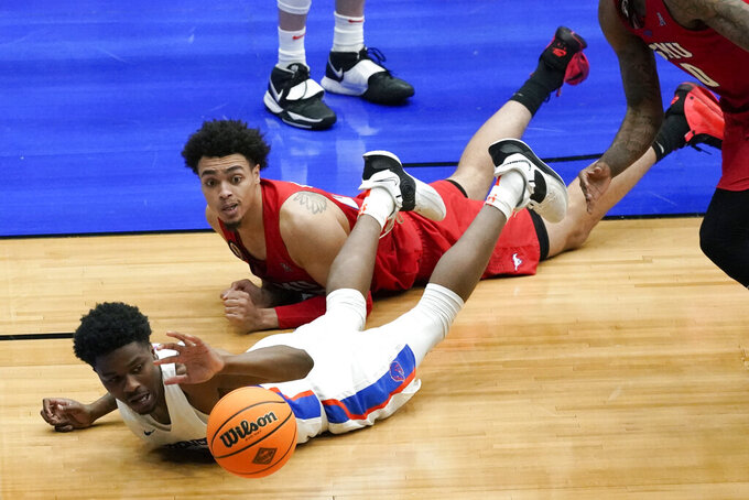 Boise State guard Devonaire Doutrive loses control of the ball ahead of SMU forward Isiah Jasey, rear, during the second half of an NCAA college basketball game in the first round of the NIT, Thursday, March 18, 2021, in Frisco, Texas. Boise State won 85-84. (AP Photo/Tony Gutierrez)