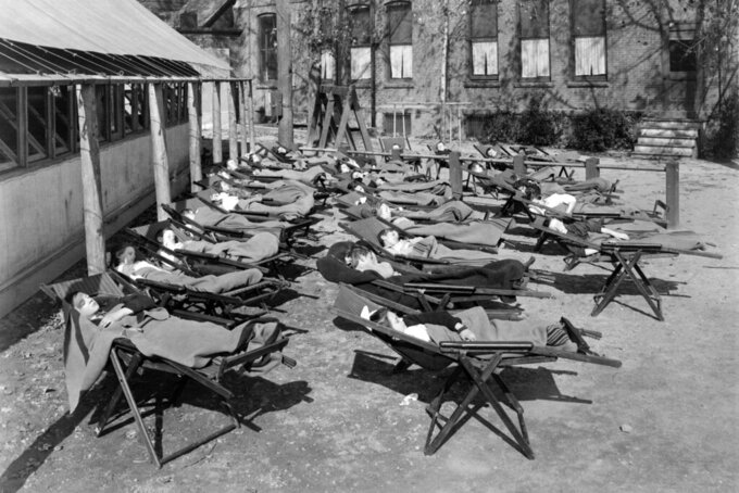 This 1912 photo from the Library of Congress shows an open air school during rest period in Rochester, N.Y. Poor ventilation in school buildings across the U.S. will limit the ability of in-person instruction to resume safely. Some districts are warming to the idea of outdoor classrooms. (Library of Congress via AP)