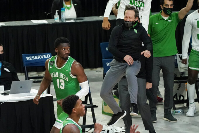 North Texas head coach Grant McCasland, right, and forward Thomas Bell (13) celebrate after Bell's 3-point basket during overtime in the championship game against Western Kentucky in the NCAA Conference USA men's basketball tournament Saturday, March 13, 2021, in Frisco, Texas. North Texas won 61-57 in overtime. (AP Photo/Tony Gutierrez)