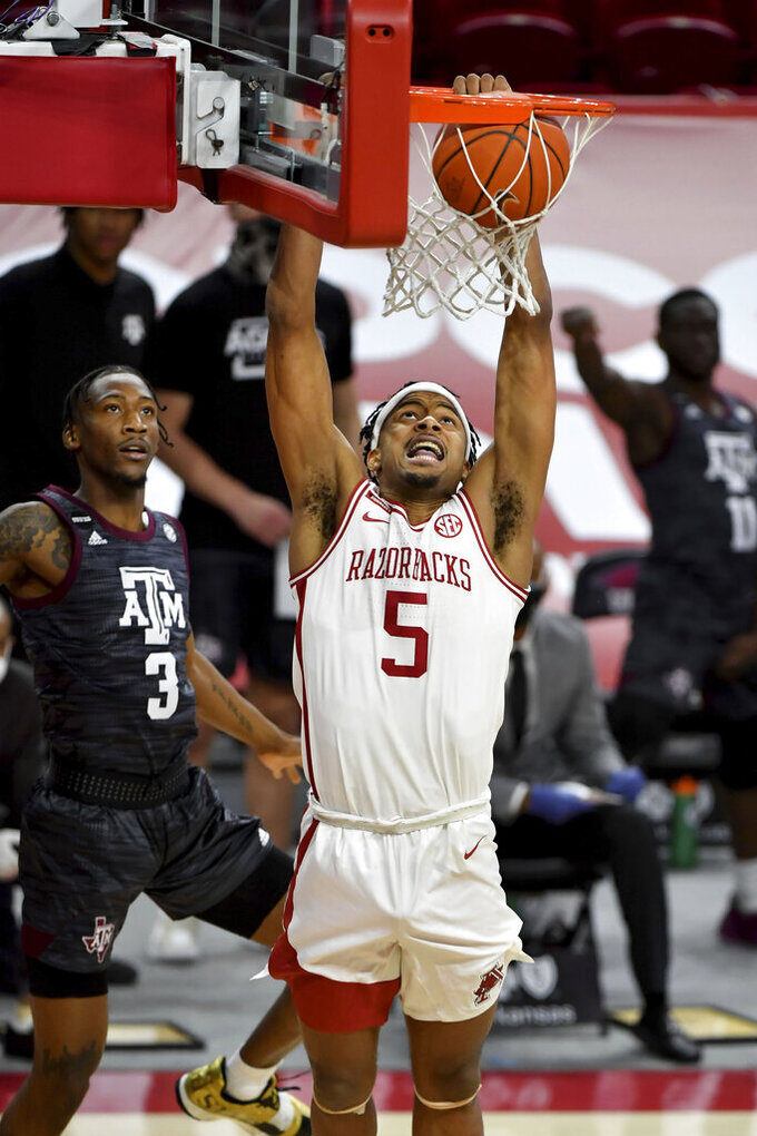 Arkansas guard Moses Moody (5) dunks in front of Texas A&M defender Quenton Jackson (3) during the first half of an NCAA college basketball game in Fayetteville, Ark. Saturday, March 6, 2021. (AP Photo/Michael Woods)