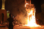 A protester takes pictures of a protest symbol that was set on fire by the supporters of former Lebanese Prime Minister Saad Hariri, after a small demonstration had denounced the naming of Hariri as a potential candidate as the country's new prime minister, in downtown Beirut, Lebanon, Wednesday, Oct. 21, 2020. Hariri resigned a year ago amid nationwide protests against government corruption and mismanagement of Lebanon's resources.  (AP Photo/Hussein Malla)