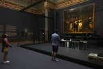 Visitors admire Rembrandt's Night Watch in the reopened Rijksmuseum in Amsterdam, Netherlands, Monday, June 1, 2020. The Dutch government took a major step to relax the coronavirus lockdown, with bars, restaurants, cinemas and museums reopening under strict conditions. (AP Photo/Peter Dejong)