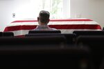 In this April 3, 2020, photo, Eric Coleman sits in front of his father's casket during his funeral, in Lexington, S.C. J. Robert Coleman's widow and three sons were spaced apart to follow social distancing guidelines during the coronavirus outbreak. (AP Photo/Sarah Blake Morgan)