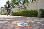 FILE - In this Aug. 25, 2020, file photo, a cyclist, wearing a mask to prevent the spread of the new coronavirus, rides by an entrance to the University of Miami in Coral Gables, Fla. The torrid coronavirus summer across the Sun Belt is easing after two disastrous months that brought more than 35,000 deaths. (AP Photo/Wilfredo Lee, File)