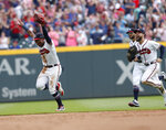 Atlanta Braves outfielders, from left, Ronald Acuna Jr. , Nick Markakis and Ender Inciarte race in to join the celebration after defeating Philadelphia Phillies 5-3 in a baseball game to clinch the National League East Division, Saturday, Sept. 22, 2018, in Atlanta.. (AP Photo/John Bazemore)