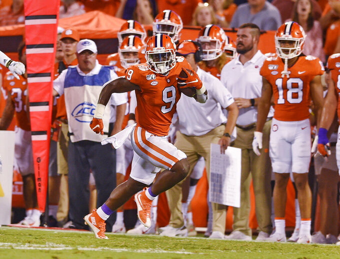 Clemson's Travis Etienne runs down the sideline for a 90-yard touchdown during the first half of the team's NCAA college football game against Georgia Tech on Thursday, Aug. 29, 2019, in Clemson, S.C. (AP Photo/Richard Shiro)
