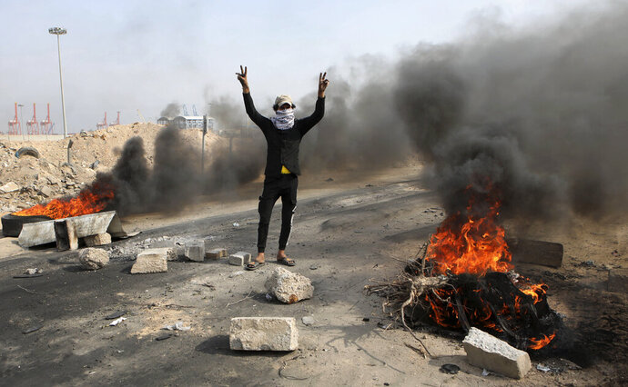 Anti-government protesters re-block the port of Umm Qasr Iraq, Thursday, Nov. 7, 2019.  Tens of thousands of people have taken to the streets in recent weeks in Iraq to protest widespread corruption, a lack of job opportunities and poor basic services, despite Iraq's vast oil reserves. (AP Photo/Nabil al-Jourani)