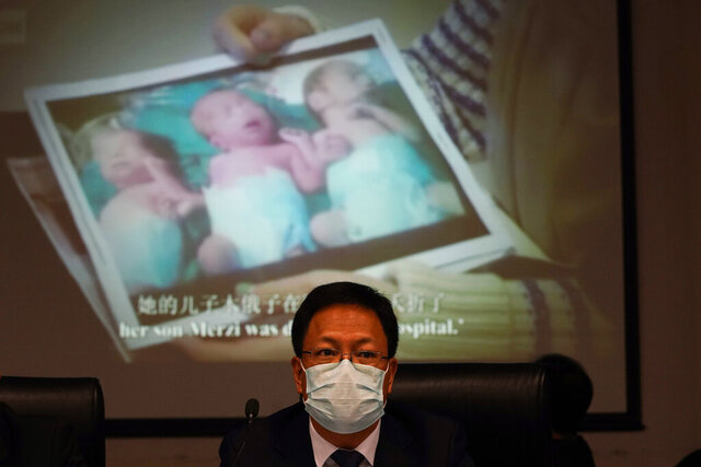 Xu Guixiang, a deputy spokesperson for the Xinjiang regional government, looks up near a slide showing a photo of Uighur infants during a press conference to refute accusations of genocide in Beijing, China. The Chinese official on Monday denied Beijing has imposed coercive birth control measures among Muslim minority women, following an outcry over a tweet by the Chinese Embassy in Washington claiming that government polices had freed women of the Uighur ethnic group from being