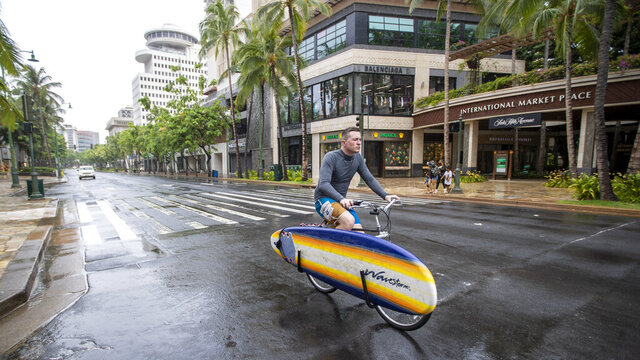 An Oahu resident packing his surfboard on his bike rides through a deserted Waikiki on Kalakaua Ave., Sunday, July 26, 2020, in Honolulu. Most of Oahu residents are taking shelter preparing for the arrival of Hurricane Douglas. (AP Photo/Eugene Tanner)
